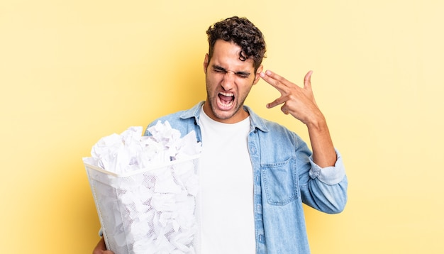 Hiszpanie przystojny mężczyzna patrząc niezadowolony i zestresowany, gest samobójczy co pistolet znak. koncepcja śmieci z kulkami papierowymi