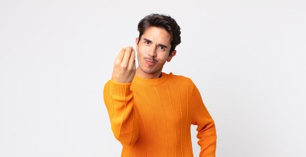 Hiszpanie przystojny mężczyzna robiący gest kaprysu lub pieniędzy, mówiący ci o spłacie długów!