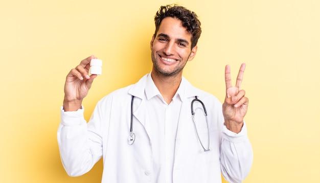 Hiszpanie przystojny mężczyzna uśmiecha się i wygląda na szczęśliwego, gestykulując zwycięstwo lub pokój. koncepcja pigułek na butelki lekarza
