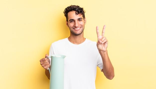 Hiszpanie przystojny mężczyzna uśmiecha się i wygląda na szczęśliwego, gestykulując zwycięstwo lub pokój. koncepcja termosu do kawy