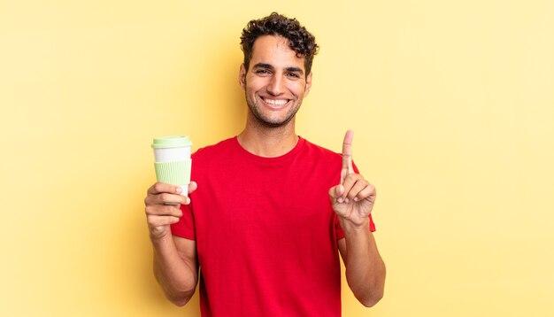 Hiszpanie przystojny mężczyzna uśmiechający się dumnie i pewnie co numer jeden. koncepcja kawy na wynos