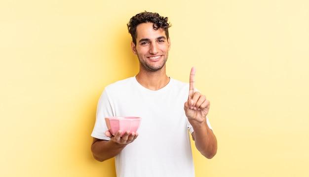 Hiszpanie przystojny mężczyzna uśmiechający się dumnie i pewnie co numer jeden. koncepcja pustej miski
