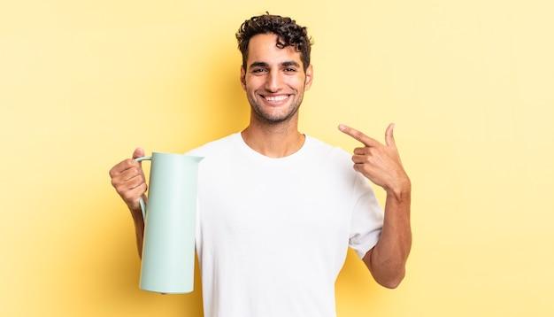 Hiszpanie przystojny mężczyzna uśmiechający się pewnie wskazując na swój szeroki uśmiech. koncepcja termosu do kawy