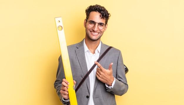 Hiszpanie przystojny mężczyzna uśmiechający się radośnie, czując się szczęśliwy i wskazując na bok. koncepcja architekta
