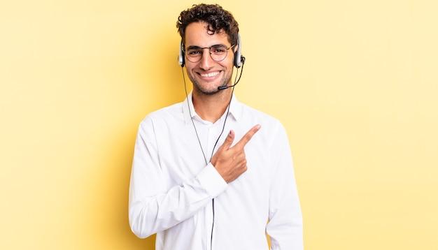 Hiszpanie przystojny mężczyzna uśmiechający się radośnie, czując się szczęśliwy i wskazując na bok. koncepcja telemarketera