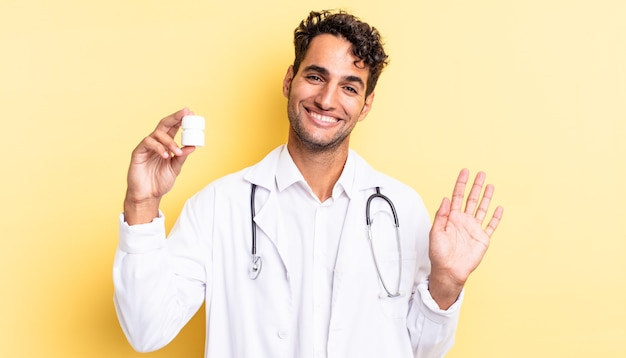 Hiszpanie przystojny mężczyzna uśmiechający się radośnie, machający ręką, witający i pozdrawiający. koncepcja pigułek na butelki lekarza