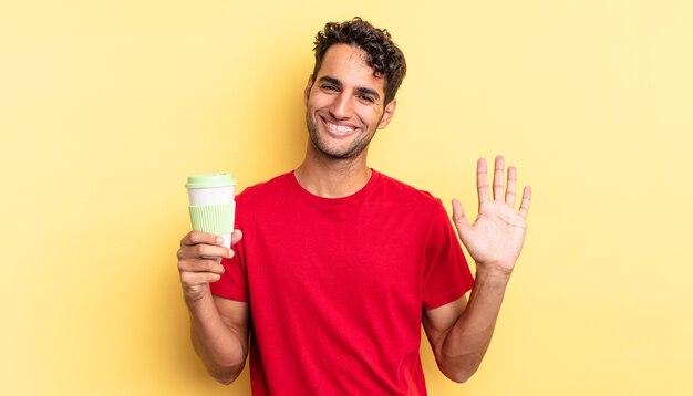 Hiszpanie przystojny mężczyzna uśmiechający się radośnie, machający ręką, witający i witający cię. koncepcja kawy na wynos