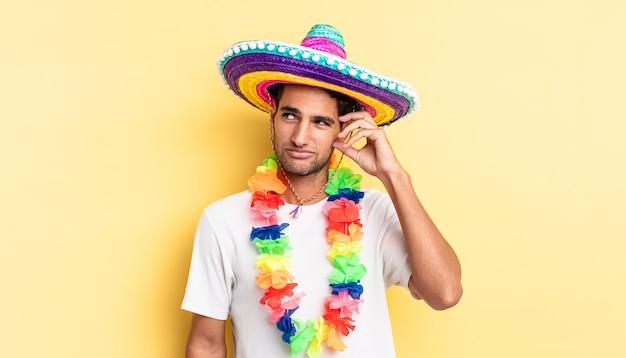 Hiszpanie przystojny mężczyzna uśmiechający się szczęśliwie i marzący lub wątpiący. koncepcja meksykańskiej imprezy