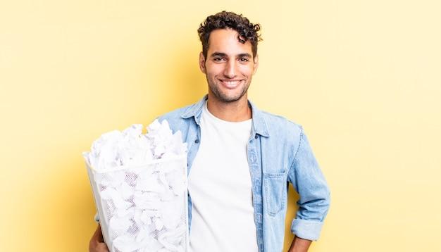 Hiszpanie przystojny mężczyzna uśmiechający się szczęśliwie z ręką na biodrze i pewny siebie. koncepcja śmieci z kulkami papierowymi