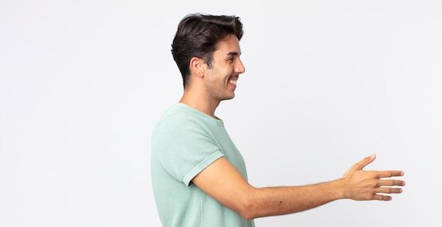 Hiszpanie przystojny mężczyzna uśmiechający się, witający cię i oferujący uścisk dłoni, aby zamknąć udaną transakcję, koncepcja współpracy