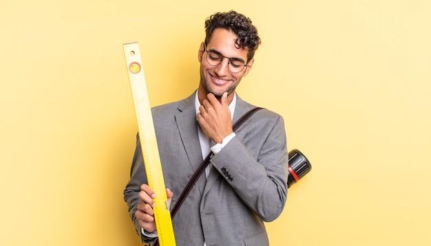 Hiszpanie przystojny mężczyzna uśmiechający się ze szczęśliwym, pewnym siebie wyrazem twarzy z ręką na brodzie. koncepcja architekta