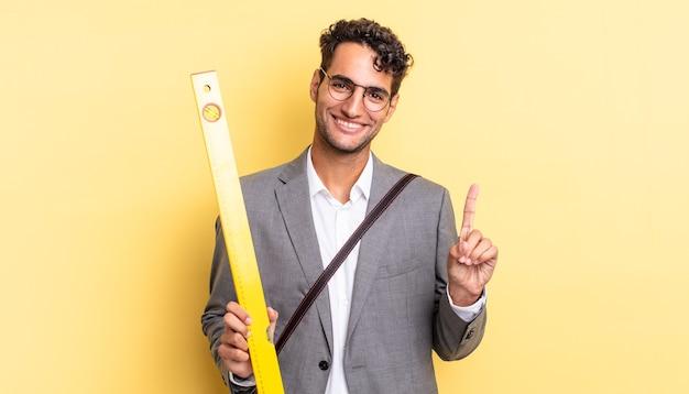 Hiszpanie przystojny mężczyzna uśmiechnięty i przyjazny, pokazując numer jeden. koncepcja architekta