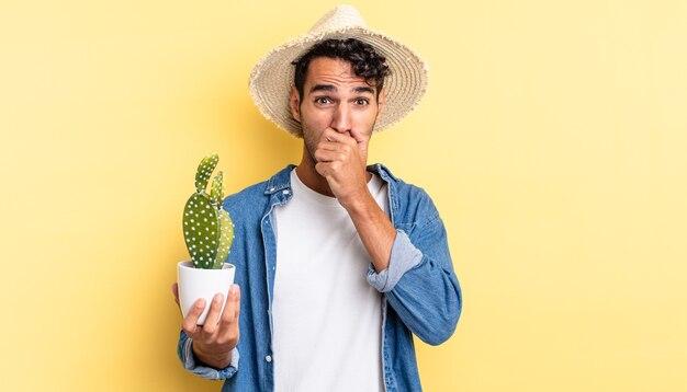 Hiszpanie przystojny mężczyzna zakrywający usta rękami z szokującą koncepcją rolnika i kaktusa