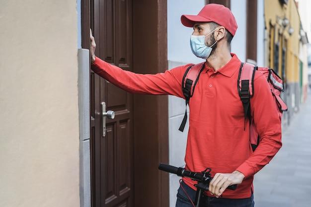Hiszpanin dostawy ze skuterem elektrycznym dzwoni do drzwi - twarz focus