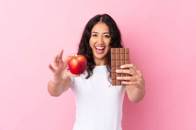 Hiszpańska chinka nad odizolowaną różową ścianą bierze czekoladową tabletkę w jednej ręce i jabłko w drugiej