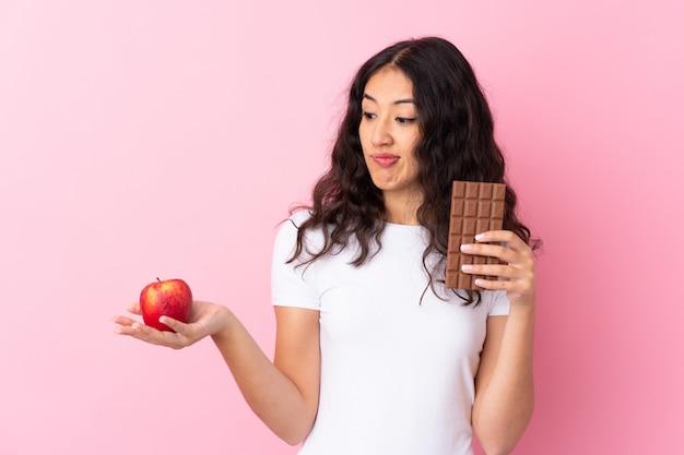 Hiszpańska chinka nad odizolowaną różową ścianą mająca wątpliwości, podczas gdy biorąc czekoladową tabletkę w jednej ręce i jabłko w drugiej
