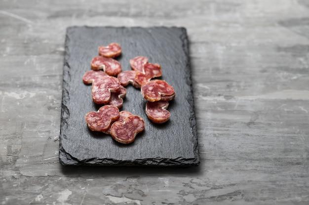 Hiszpańska kiełbasa fuet na czarnej płycie ceramicznej