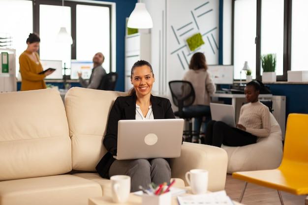 Hiszpańska kobieta biznesu uśmiecha się do kamery, siedząc na kanapie, pisząc na laptopie, podczas gdy różni koledzy pracują w tle