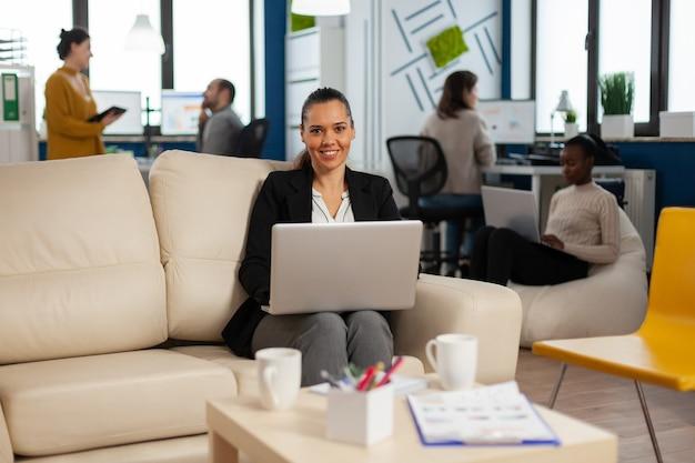 Hiszpańska kobieta biznesu uśmiecha się do kamery trzymającej laptopa