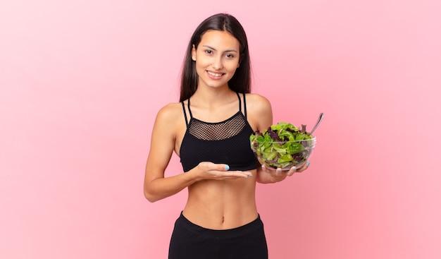 Hiszpańska kobieta fitness uśmiecha się radośnie, czuje się szczęśliwa, pokazuje koncepcję i trzyma sałatkę