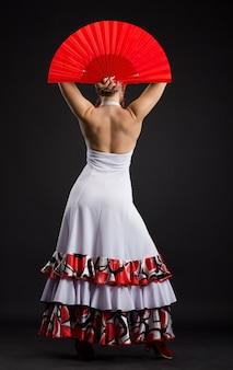 Hiszpańska kobieta tańczy flamenco na ciemnym tle