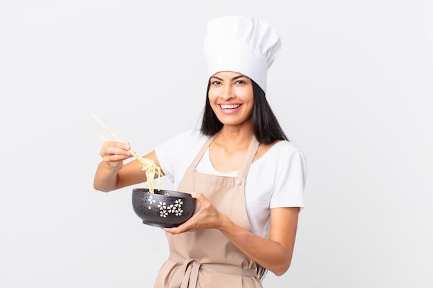 Hiszpańska ładna kucharz kobieta trzyma miskę z makaronem