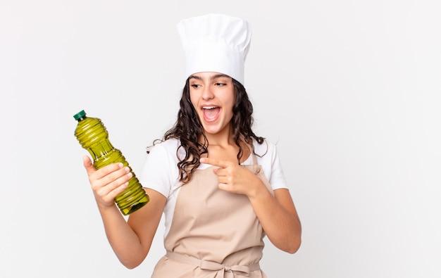 Hiszpańska ładna szefowa kuchni trzymająca butelkę oliwy z oliwek?