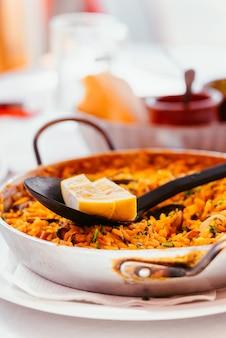 Hiszpańska paella z owocami morza z małżami, krewetkami i kawałkiem cytryny. w stalowej patelni paella. kanaryjska kuchnia w małej rodzinnej restauracji.