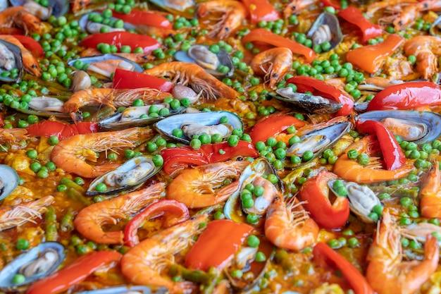 Hiszpańska paella z owoców morza na patelni z małżami, krewetkami i warzywami. owoce morza paella tło, zbliżenie, tradycyjne hiszpańskie danie z ryżu