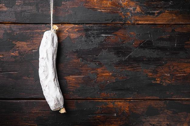 Hiszpańska sucha kiełbasa salchichon na starym drewnianym stole, widok z góry z miejscem na tekst.