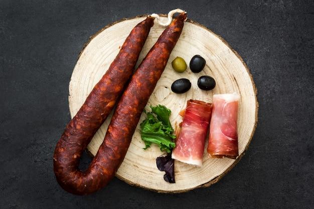 Hiszpańska szynka serrano, oliwki i kiełbasa na łupkowej powierzchni