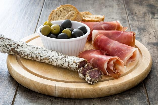 Hiszpańska szynka serrano, oliwki i kiełbaski na drewnie