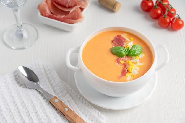 Hiszpańska zupa salmorejo z puree z surowych pomidorów ozdobiona bazylią i gotowanym jajkiem w misce