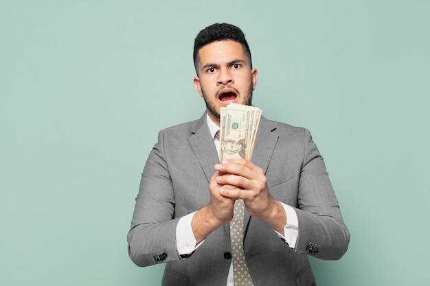 Hiszpanski biznesmen przestraszony wyrazem twarzy i trzymający banknoty dolarowe
