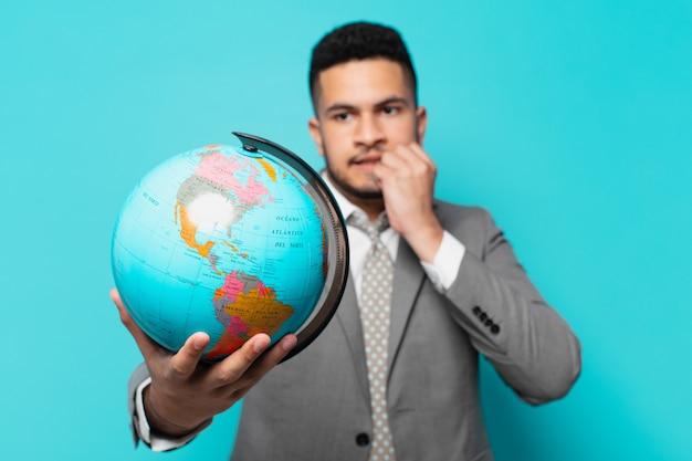 Hiszpanski biznesmen przestraszony wyrazem twarzy i trzymający model planety świata