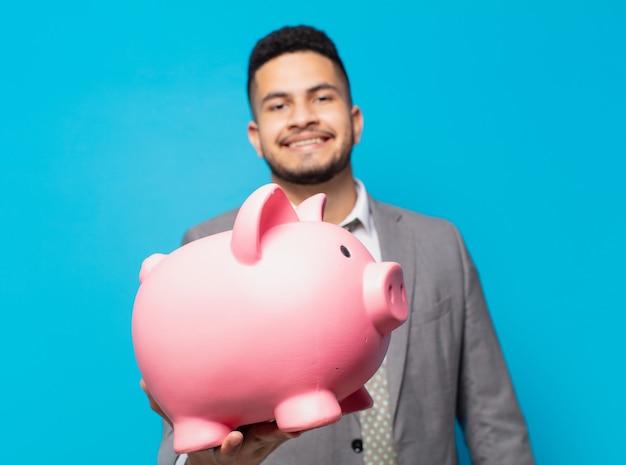 Hiszpanski biznesmen szczęśliwy wyraz twarzy i trzymający skarbonkę