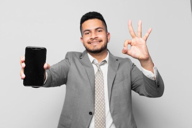 Hiszpański biznesmen szczęśliwy wyraz twarzy i trzymający telefon