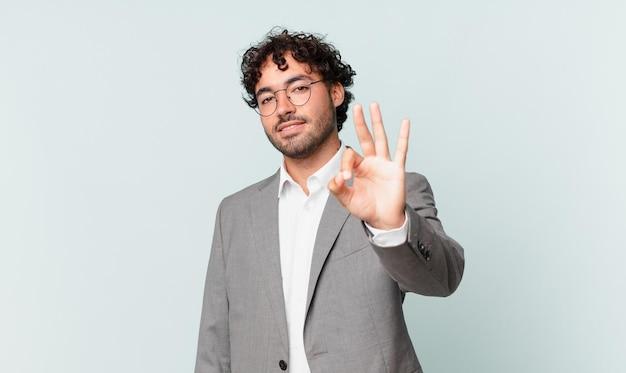 Hiszpański biznesmen uśmiechnięty i wyglądający przyjaźnie, pokazujący numer trzy lub trzeci z ręką do przodu, odliczający w dół