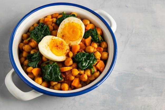 Hiszpański chickpea i szpinak gulasz z jajkami na jasnopopielatym tle. kuchnia hiszpańska.