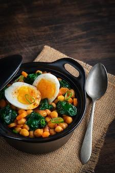 Hiszpański chickpea i szpinaka gulasz z jajkami na nieociosanym drewnianym tle. kuchnia hiszpańska.
