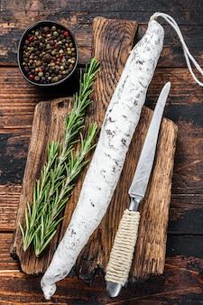 Hiszpański fuet salami wurst na drewnianej desce do krojenia.