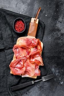 Hiszpański jamon serrano, szynka. czarne tło, widok z góry