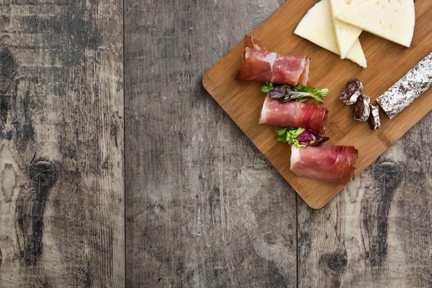 Hiszpański serrano baleron, ser i kiełbasa na nieociosanej drewnianej stół kopii przestrzeni