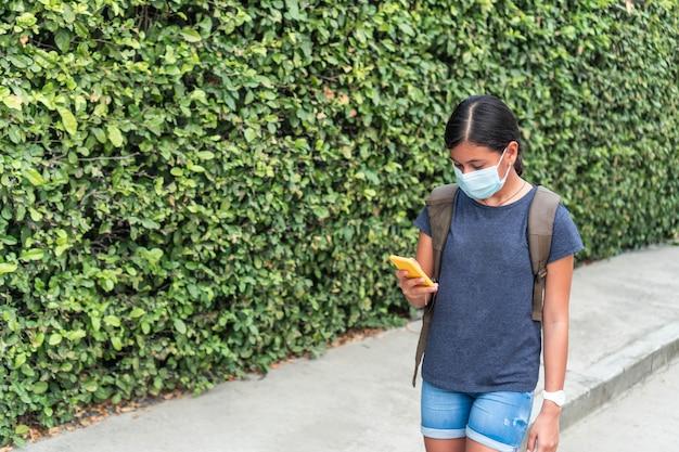Hiszpanski student noszący maskę ochronną podczas rozmowy wideo z przyjacielem na ulicy