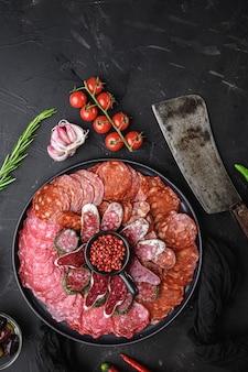 Hiszpański talerz wędlin, chorizo, fuet, lomo, longaniza i salchichon na czarnym stole, widok z góry.