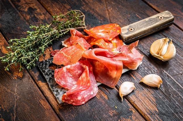 Hiszpańskie salami wędliniarskie, jamon, kiełbaski peklowane choriso na tasaku. ciemne drewniane tło. widok z góry.