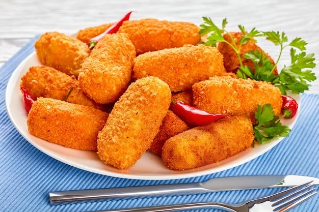 Hiszpańskie smażone w głębokim tłuszczu złotobrązowe krokiety ziemniaczane, krokiety na białym talerzu na drewnianym stole z widelcem i nożem