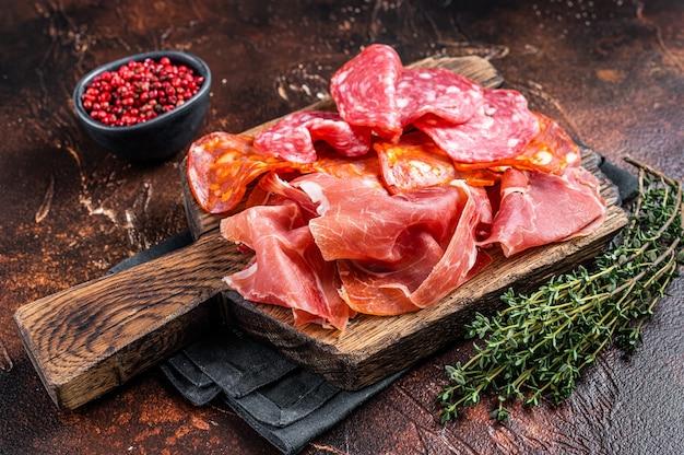 Hiszpańskie tapas mięsne - salami, jamon, kiełbaski peklowane choriso. ciemne tło. widok z góry.