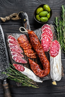 Hiszpańskie tapas pokrojone kiełbaski salami, fuet i chorizo na drewnianej desce do krojenia