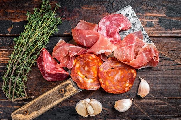 Hiszpańskie wędliny salami, jamon, kiełbaski choriso na tasaku do mięsa. ciemny drewniany stół. widok z góry.